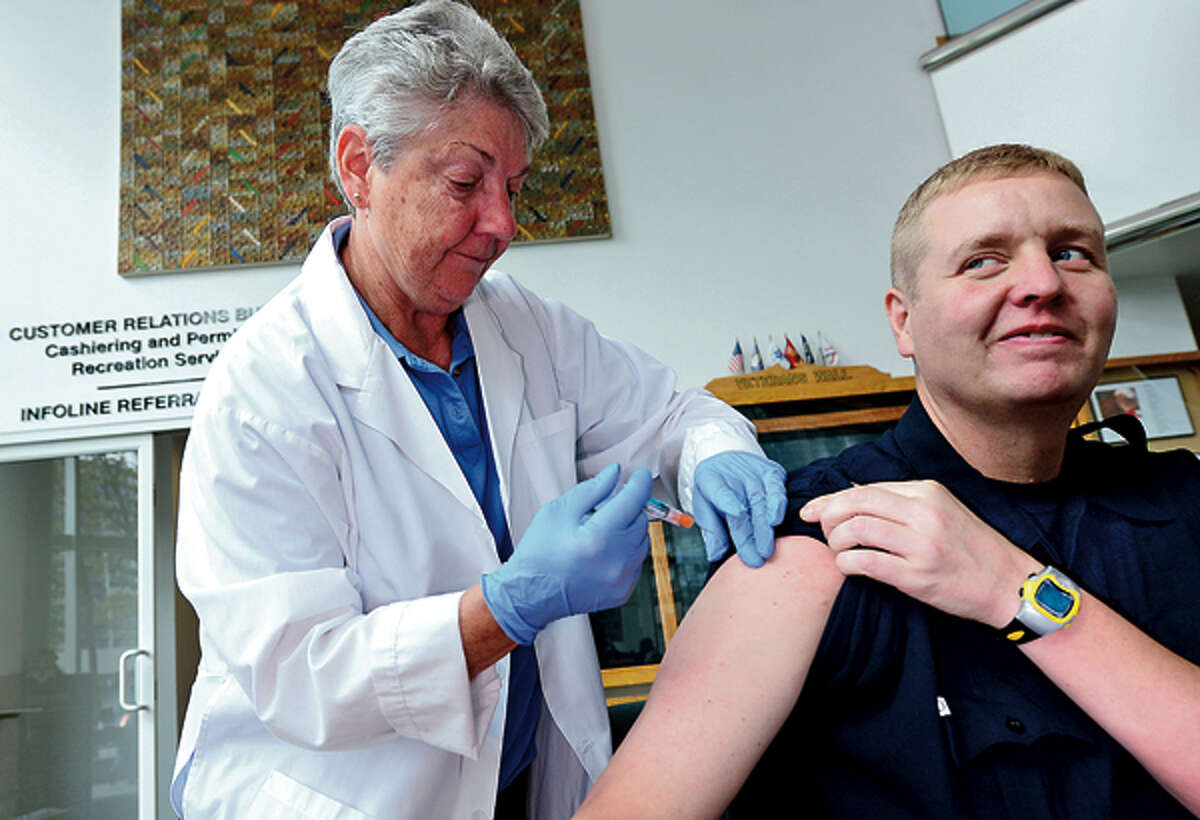 Public Health Nurse, Mary Ann Williams gives Stamford firefighter, Chris Brennan, a flu shot during the Stamford Hospital and The City of Stamford Department of Health and Social Services kick off press conference for their annual joint
