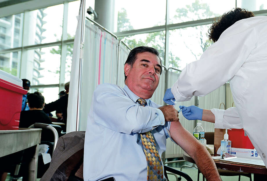 "Stamford mayor Michael Pavia receives a flu shot during the Stamford Hospital and The City of Stamford Department of Health and Social Services kick off press conference for their annual joint ""Fight the Flu"" campaign on Tuesday at the Stamford Government Center. Hour photo / Erik Trautmann / (C)2012, The Hour Newspapers, all rights reserved"