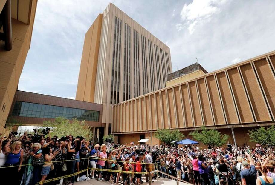 Spectators wait outside Superior Court in Phoenix, Wednesday, May 8, 2013 for a verdict in the trial of Jodi Arias, a waitress and aspiring photographer charged with killing her boyfriend, Travis Alexander, in Arizona in 2008. The four month trial included graphic details of their sexual escapades and photos of Alexander just after his death. (AP Photo/Matt York) / AP