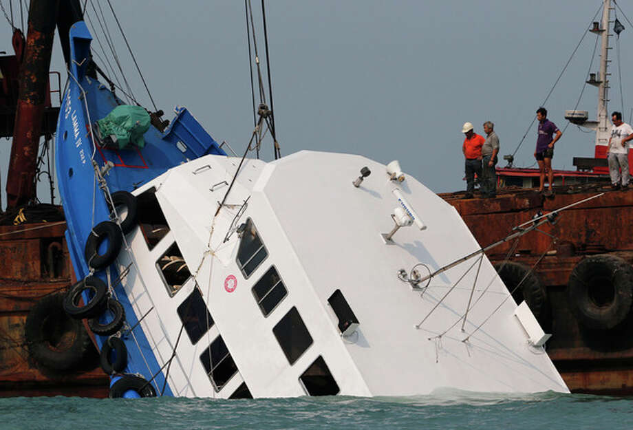Officials check on a half submerged boat after it collided Monday night near Lamma Island, off the southwestern coast of Hong Kong Island Tuesday Oct. 2, 2012. The boat packed with revelers on a long holiday weekend collided with a ferry and sank off Hong Kong, killing at least 36 people and injuring dozens, authorities said. (AP Photo/Vincent Yu) / AP