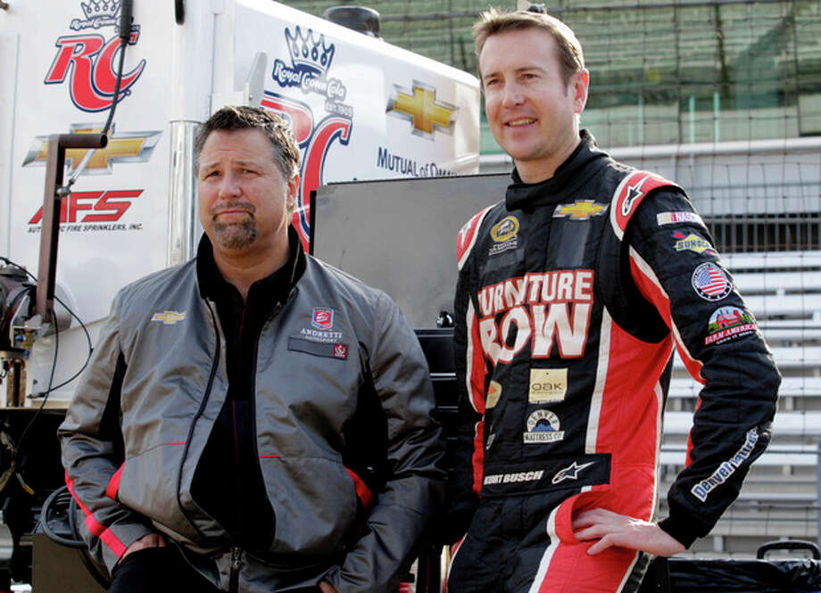 Andretti Autosport team owner Michael Andretti, left, and NASCAR driver Kurt Busch wait for the start of a testing session at the Indianapolis Motor Speedway in Indianapolis, Thursday, May 9, 2013. Busch was driving an Indycar for the first time during the test. (AP Photo/AJ Mast) / FR123854 AP