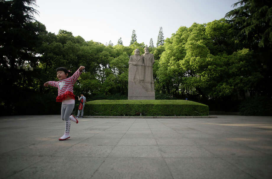 In this May 4, 2012 photo, a girl gestures in front of the statue of of Karl Marx, left, and Frederick Engels, right, the founders of communism, at Fuxing Park in Shanghai, China. Fuxing Park, southwest of People's Square on the opposite side of the North-South Expressway, is a French-style park with fountains and gardens that once was part of the French Concession neighborhood during Shanghai's colonial era. In the mornings, locals dance and practice tai-chi or martial arts here. (AP Photo/Eugene Hoshiko) / AP