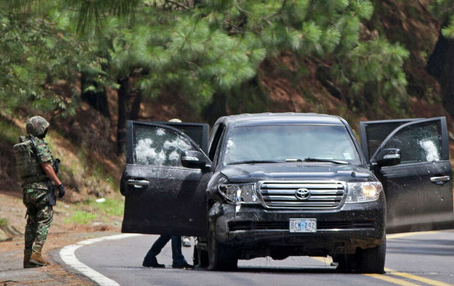 FILE - In this Aug. 24, 2012. file photo, an armored U.S. embassy vehicle is checked by military personal after it was attacked by unknown assailants on the highway leading to the city of Cuernavaca, near Tres Marias, Mexico. A senior U.S. official says there is strong circumstantial evidence that Mexican federal police who fired on a U.S. embassy vehicle, wounding two CIA agents, were working for organized crime on a targeted assassination attempt. (AP Photo/Alexandre Meneghini, File) / AP