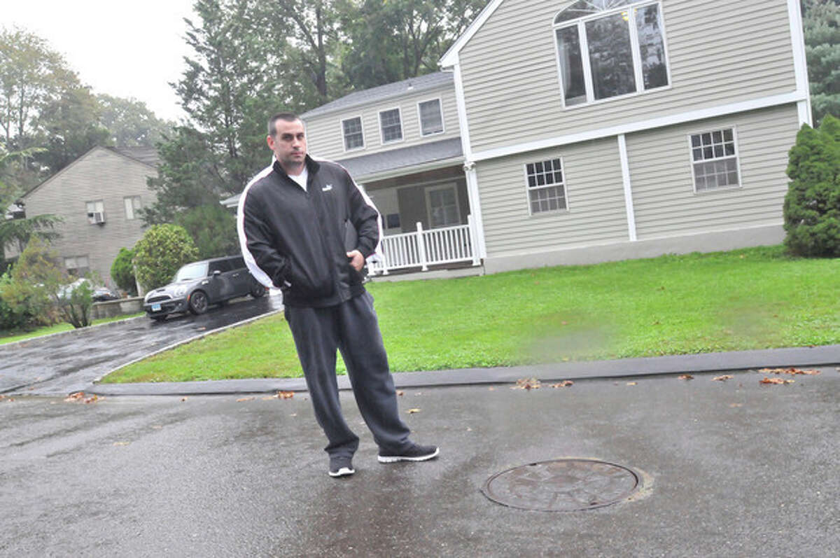 Hour photos / Matthew Vinci Angelo DiPasquale of Norwalk stands Tuesday in front of his Saddle Road home where water from the storm drain at the foot of his driveway and sewer manhole near him floods his property during storms.