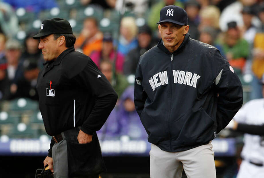 New York Yankees manager Joe Girardi, right, reacts after arguing with home plate umpire Phil Cuzzi, who called Colorado Rockies runner Dexter Fowler safe at home as he scored on a sacrifice fly in the first inning of a baseball game in Denver on Thursday, May 9, 2013. (AP Photo/David Zalubowski) / AP
