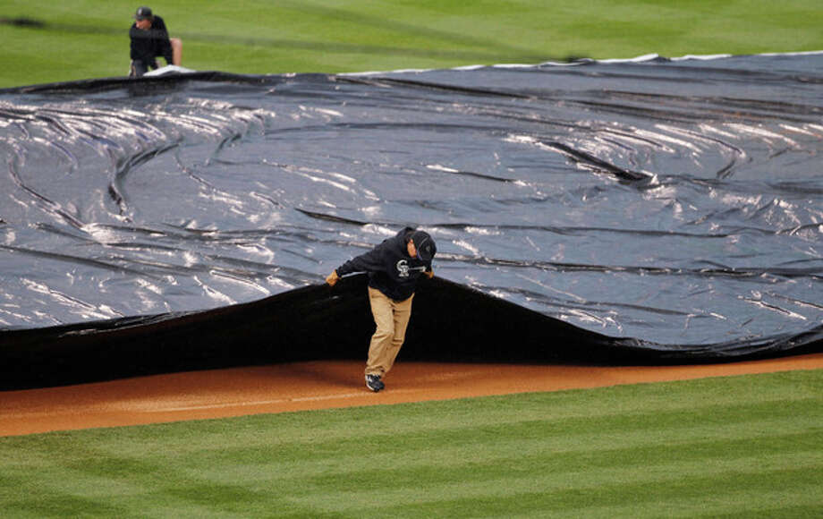 Field crew members pull the tarpaulin as heavy rains sweep over Coors Field and halt play in the fourth inning of a baseball game between the New York Yankees and Colorado Rockies in Denver on Thursday, May 9, 2013. (AP Photo/David Zalubowski) / AP