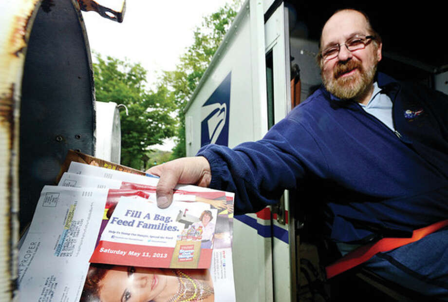 "Wilton USPS mail carrier Alan Horowitz delivers cards asking people to donate food for the ""Stamp Out Hunger Food Drive"" which is part of a national initiative raising nonperishable food items for food pantries.Hour photo / Erik Trautmann / (C)2013, The Hour Newspapers, all rights reserved"