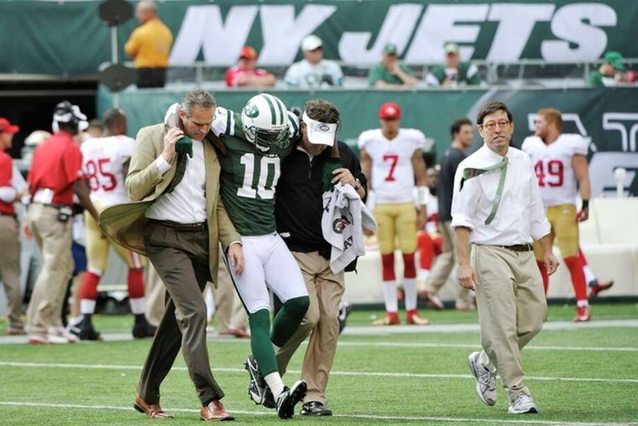 New York Jets wide receiver Santonio Holmes (10) is helped off the field after being injured during the second half of an NFL football game against the San Francisco 49ers Sunday, Sept. 30, 2012, in East Rutherford, N.J. (AP Photo/Bill Kostroun) / FR59151 AP