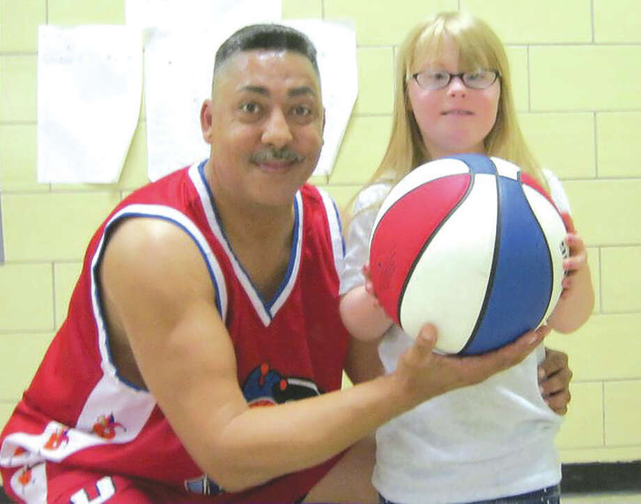Contributed photoDaryl Hanson, a former Brien McMahon basketball star who has played for the Harlem Globetrotters, holds up a basketball for one of the special needs youngsters in attendance at one of his programs for youth.