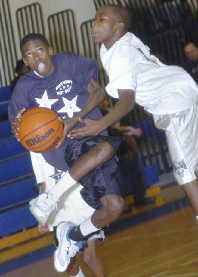 Two middle school players battle during the initial 'Shoot Hoops, Not Guns' tournament back in 2007. The event returns to Norwalk this weekend with two days of action at Brien McMahon High School.@Cutline Byline:Hour photo/Matthew Vinci