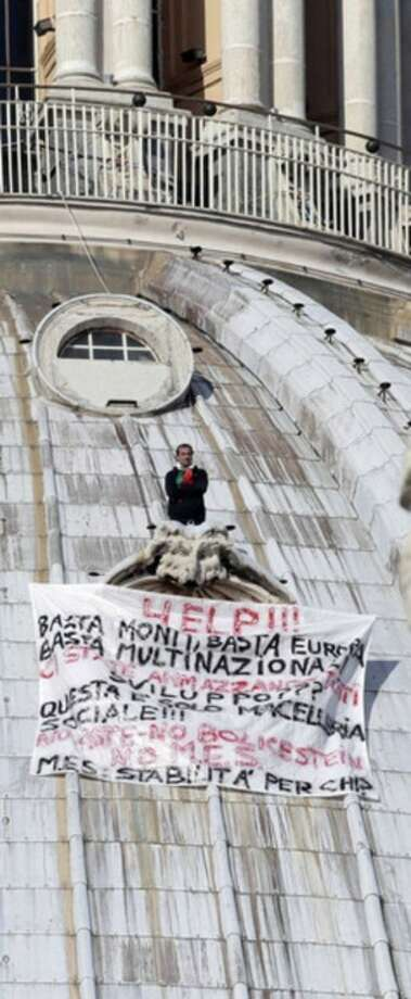 "Ap photoFirefighters look at Italian businessman Marcello di Finizio standing above his banner which reads in Italian ""Help!! Enough Monti (Italian Premier Mario Monti), enough Europe, enough multinationals, you are killing all of us. Development?? This is a social butchery!"", as he protests on St. Peter's 130-meter-high (42-feet-high) dome, at the Vatican, Wednesday."