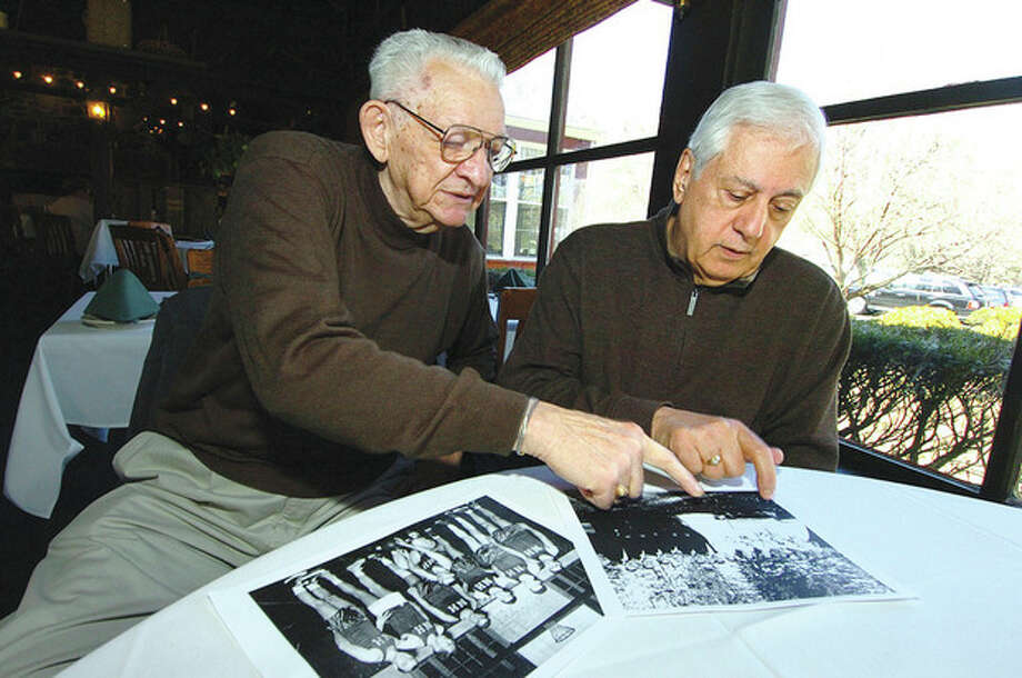 Hour photo/Alex von KleydorffLongtime friends and former teammates Joe DeFelice, left, and Tony Bartolo look over some photos from days gone by during a recent meeting in Westport. / 2013 The Hour Newspapers