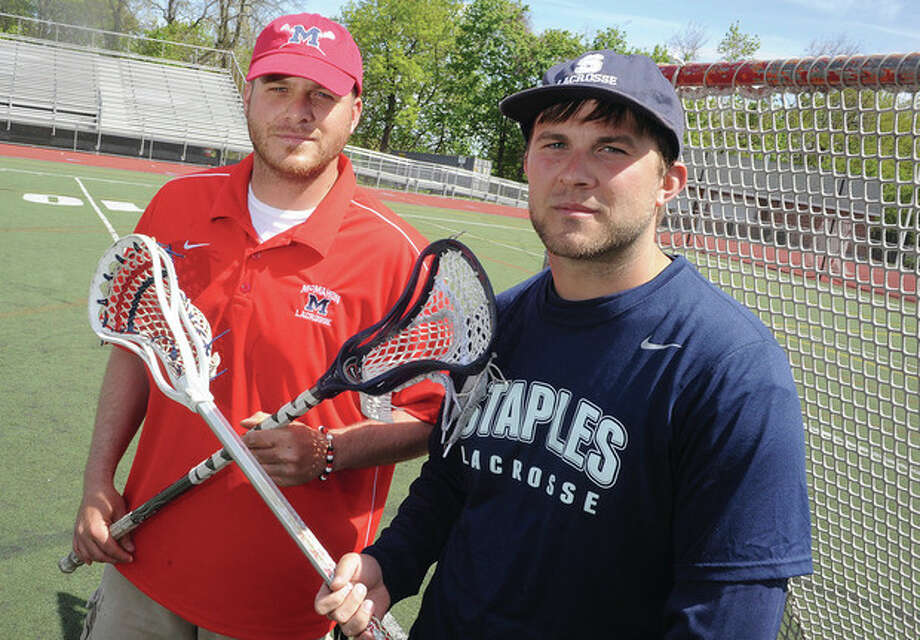 Hour photo/Matthw VinciJoey Smith, left and his younger brother, Drew, will be patrolling opposite sidelines during Thursday night's boys lacrosse game between Brien McMahon and Staples. Joey is a McMahon assistant coach and Drew is an assistant on the Staples staff.