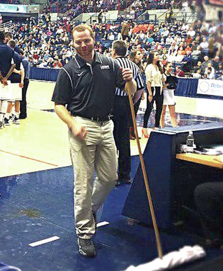 Contributed photoFormer Brien McMahon athlete Trevor Kline stands next to the basketball court at UConn's Gampel Pavilion, where he works on the crew that takes care of the court.