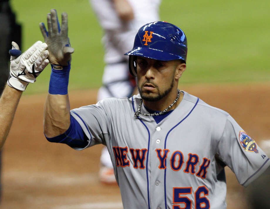 New York Mets' Andres Torres gets a high-five after batting a solo home run against the Miami Marlins in the third inning of a baseball game in Miami, Wednesday, Oct. 3, 2012. (AP Photo/Alan Diaz) / AP