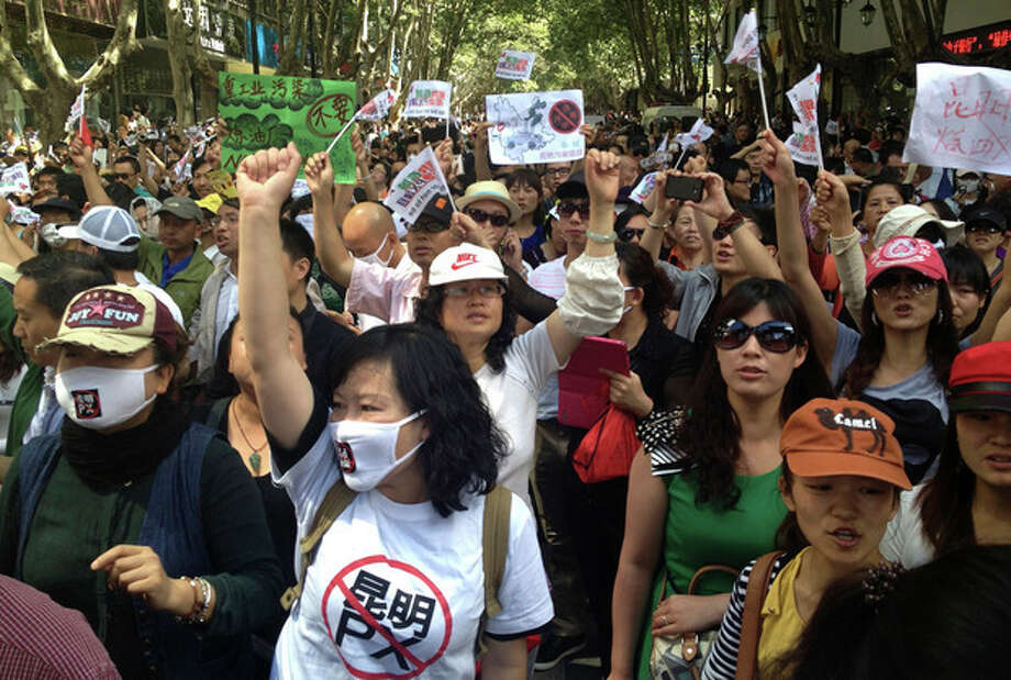 "Chinese demonstrators shout slogans during a protest against a planned refinery project in downtown Kunming in southwest China's Yunnan province, Thursday, May 16, 2013. About 2,000 demonstrators concerned about pollution took to the streets in southern China to protest plans for a planned refinery on the outskirts of Kunming. Placards and T-shirts read: ""The placards read: ""No to Kunming PX, (paraxylene)."" (AP Photo/Aritz Parra) / AP"