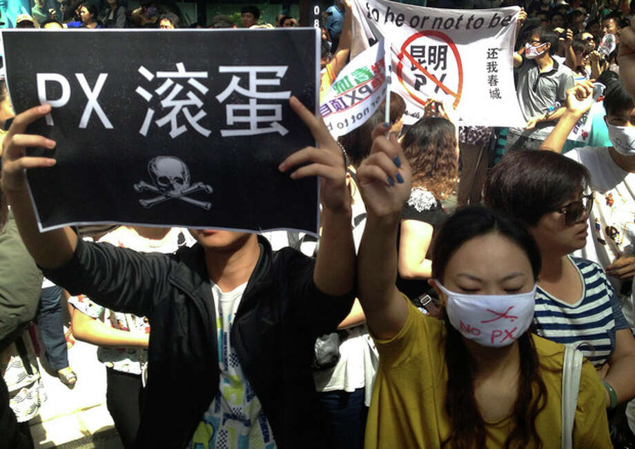"""Chinese demonstrators hold banners as they take part in a protest against a planned refinery project in downtown Kunming in southwest China's Yunnan province Thursday, May 16, 2013. About 2,000 demonstrators concerned about pollution have taken to the streets in southern China to protest plans for a planned refinery on the outskirts of the city of Kunming. The placards read: """"No to Kunming PX, (paraxylene)."""" (AP Photo/Aritz Parra) / AP"""