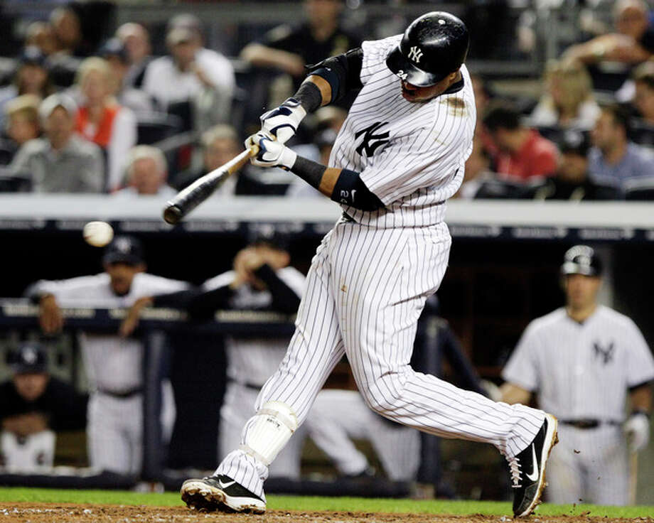 New York Yankees' Robinson Cano hits a two-RBI single during the sixth inning of a baseball game against the Boston Red Sox, Wednesday, Oct. 3, 2012, in New York. Russell Martin and Ichiro Suzuki scored on the hit. (AP Photo/Frank Franklin II) / AP