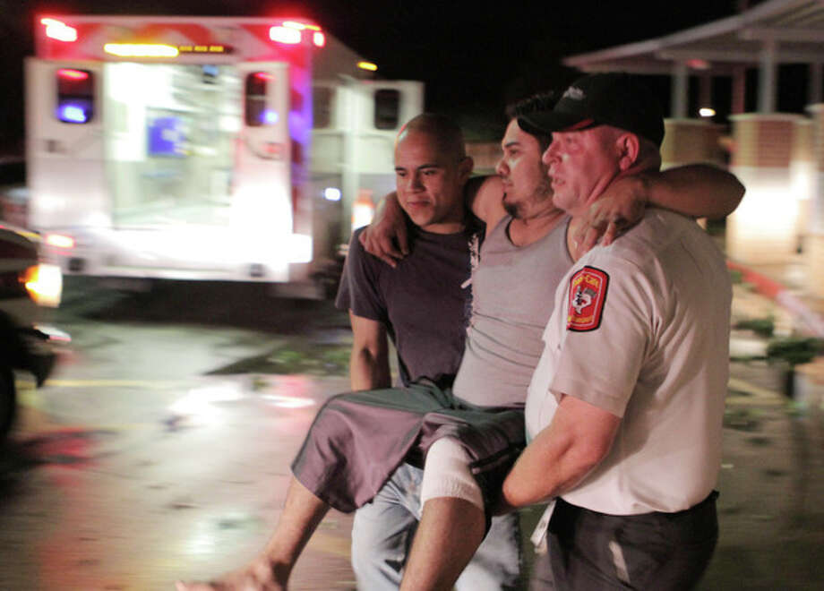 """Johnny Ortiz, left, and James South, right, carry Miguel Morales, center, who was injured in a tornado, to an ambulance in Granbury, Texas, on Wednesday May 15, 2013. Officials report the tornado caused """"multiple fatalities"""" as it tore through two neighborhoods of a North Texas town. Hood County sheriff's Lt. Kathy Jiveden reported the multiple fatalities, but she had no estimate of dead or injured. (AP Photo/Mike Fuentes) / FR103746 AP"""