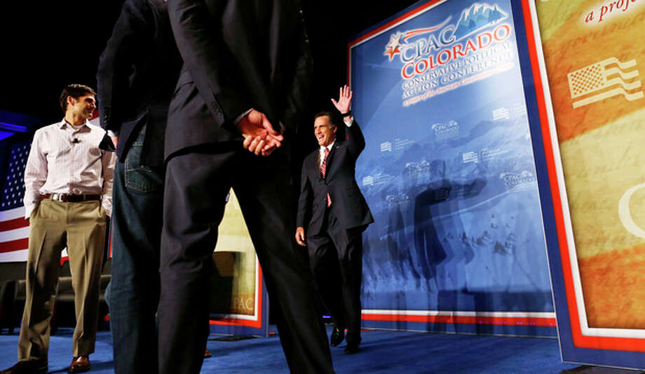 Introduced by his sons, Republican presidential candidate, former Massachusetts Gov. Mitt Romney makes a surprise appearance at a Colorado Conservative Political Action Committee (CPAC) meeting in Denver, Thursday, Oct. 4, 2012. At left is son Matt Romney. (AP Photo/Charles Dharapak) / AP