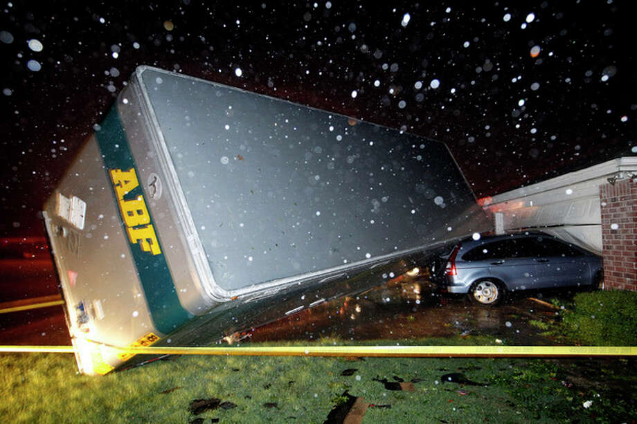 A trucking company trailer landed on a car that was parked in front of a Lindsey Ln. home in Cleburne Texas after a powerful storm went through Wednesday night, May 15, 2013. Neighbors say the trailer was parked on the street and was rolled over onto the car. (AP Photo/The Dallas Morning News, Tom Fox) / Dallas Morning News