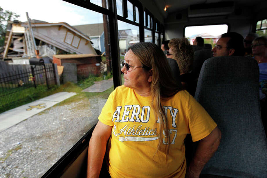 Kathy Stewart, of Enfield, Ill., looks at a blighted home as the tour bus she is riding in passes through the Upper 9th Ward in New Orleans, Tuesday, Oct. 2, 2012. Residents and the City of New Orleans may be pushing back against tour companies ushering out-of-towners into to the Lower 9th Ward, the neighborhood made famous when floodwalls and levees failed in 2005, pushing homes off their foundations and stranding residents on rooftops. (AP Photo/Gerald Herbert) / AP