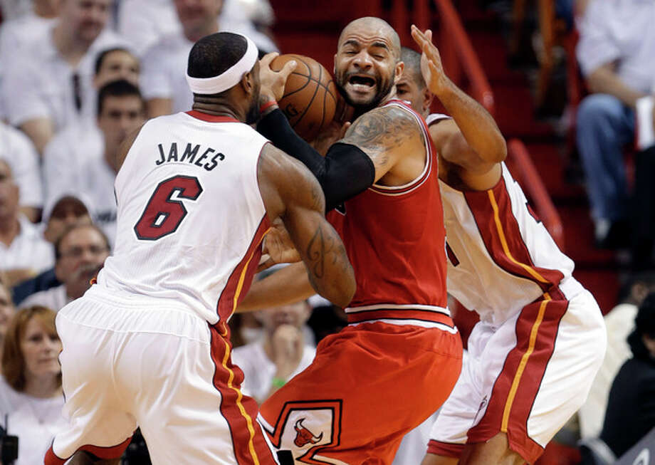 Chicago Bulls' Carlos Boozer, center, works the ball between Miami Heat's LeBron James (6) and Shane Battier, right, as he attempts to shoot during the first half of Game 5 of an NBA basketball Eastern Conference semifinal, Wednesday, May 15, 2013, in Miami. (AP Photo/Wilfredo Lee) / AP