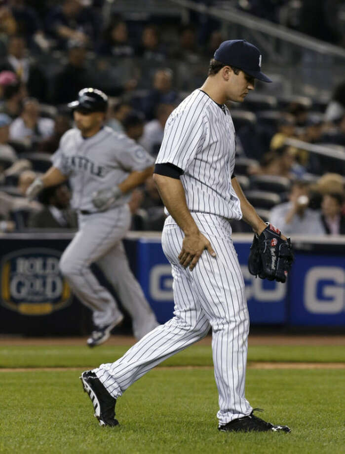 New York Yankees pitcher Brett Marshall, right, looks down after Seattle Mariners' Raul Ibanez, rear, hit a two-run home run during the fifth inning of a baseball game at Yankee Stadium in New York, Wednesday, May 15, 2013. (AP Photo/Julio Cortez)