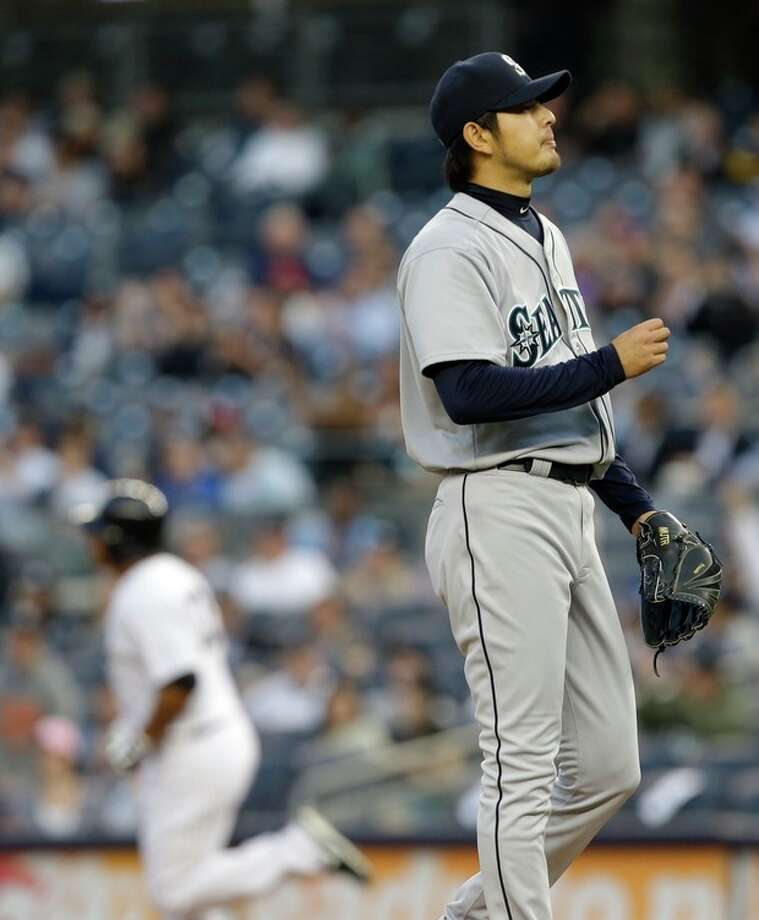 Seattle Mariners starting pitcher Hisashi Iwakuma, right, looks away as New York Yankees' Vernon Wells rounds the bases after hitting a home run during the first inning of a baseball game at Yankee Stadium in New York, Wednesday, May 15, 2013. (AP Photo/Julio Cortez) / AP