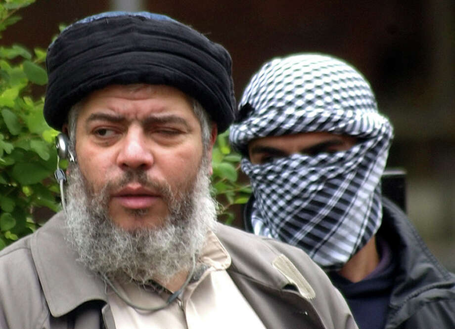 FILE - This Friday, April 30, 2004 file photo shows Muslim cleric Abu Hamza al-Masri, as he arrives with a masked bodyguard, right, to conduct Friday prayers in the street outside the closed Finsbury Park Mosque in London. A British court is expected to rule on whether extremist cleric Abu Hamza al-Masri is too ill to be extradited to the United States to face terror charges. London's High Court is set to decide Friday Oct. 5, 2012 whether al-Masri and other terror suspects can be sent to the U.S. to face charges that include helping set up a terrorist training camp in rural Oregon. (AP Photo/Max Nash, File) / AP