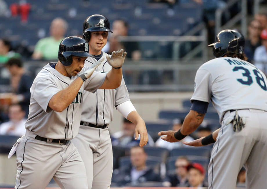 Seattle Mariners' Raul Ibanez, left, is congratulated by Michael Morse, right, after hitting a grand slam off New York Yankees starting pitcher Phil Hughes during the first inning of a baseball game at Yankee Stadium in New York, Wednesday, May 15, 2013. (AP Photo/Julio Cortez) / AP