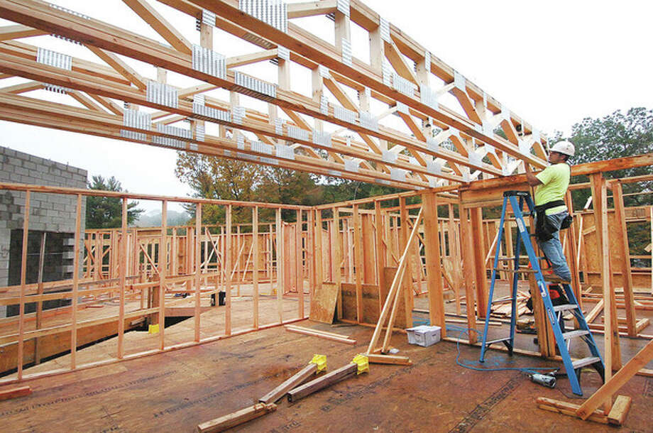 Hour photo / Alex von KleydorffFramers install a truss in one of the third-floor residential units as construction on Wilton Commons continues. / 2012 The Hour Newspapers