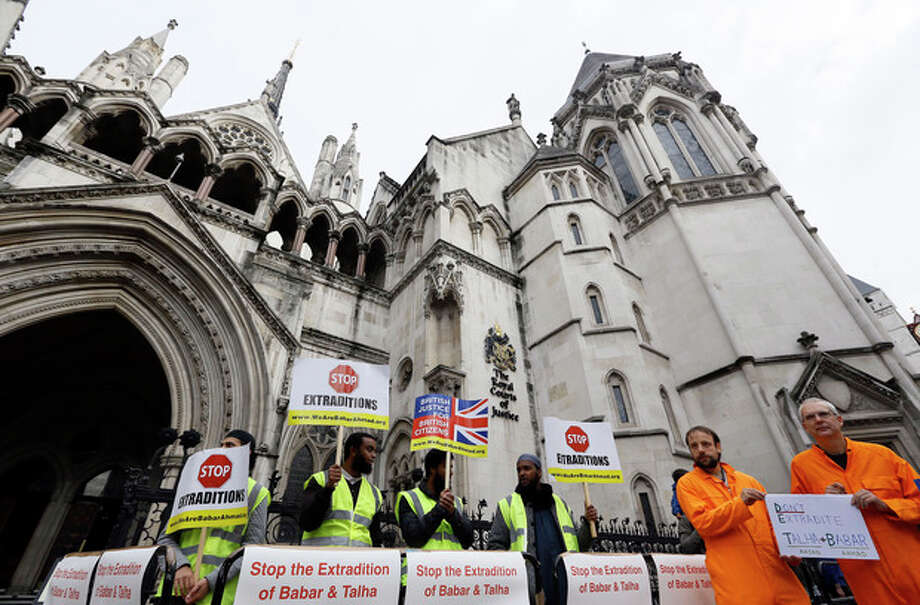 Demonstrators hold banners outside The Royal Courts of Justice in London Friday, Oct. 5, 2012. Babar Ahmad and Syed Talha Ahsan, along with Radical Islamic cleric Abu Hamza al-Masri and two other terror suspects are expected to find out today if they have won their latest legal move to avoid extradition from the UK to America for trial on terrorism charges. (AP Photo/Kirsty Wigglesworth) / AP