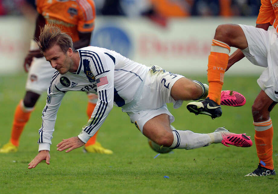 Los Angeles Galaxy midfielder David Beckham takes a fall during the first half of their MLS Cup soccer match against the Houston Dynamo, Saturday, Dec. 1, 2012, in Carson, Calif. (AP Photo/Mark J. Terrill) / AP