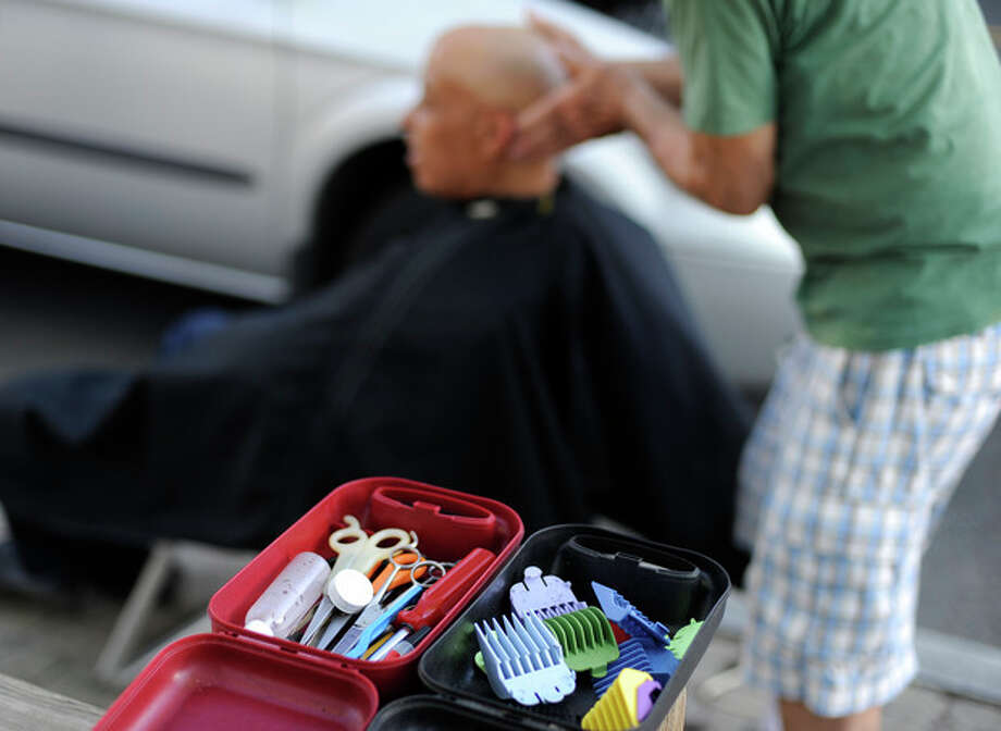 In this Wednesday, May 1, 2013 photo, clipper attachments and scissors remain within reach as Anthony Cymerys, known as Joe the Barber, works on a client in Hartford, Conn. Cymerys runs a mobile alfresco barbershop, using a car battery and power inverter to power his clippers. His fee is always the same: A hug for a haircut. (AP Photo/Jessica Hill) / FR125654 AP