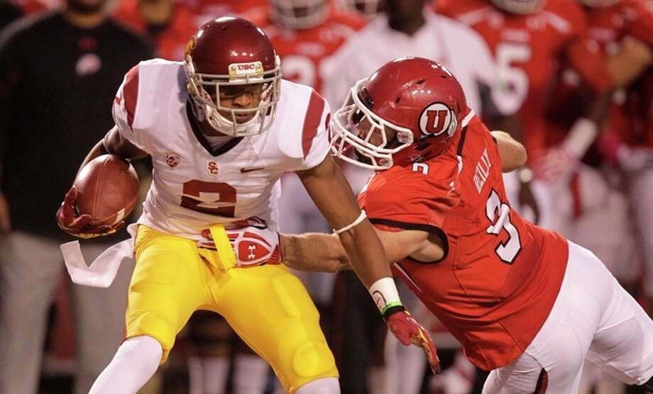 Southern California wide receiver Robert Woods (2) carries the ball as he breaks a tackle from Utah linebacker Trevor Reilly (9) in the first quarter during an NCAA college football game Thursday, Oct. 4, 2012, in Salt Lake City. (AP Photo/Rick Bowmer) / AP