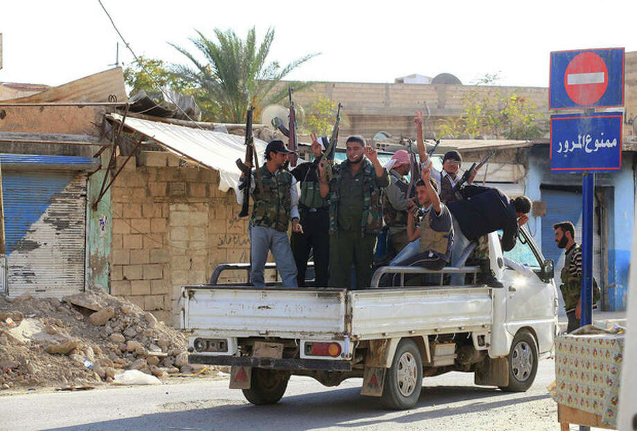 Syrian rebels ride on the back of a truck in Tel Abyad, Syria, Friday, Oct. 5, 2012. On Friday, a Syrian mortar round hit inside Turkey, causing no injuries, and Turkish troops returned fire, the state-run news agency Anadolu said late Friday, and Turkey deployed more troops near to the border with Syria. (AP Photo) / AP