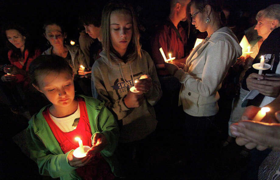 Family members of Border Patrol Agent Nicholas Ivie participate in Thursday Oct. 4, 2012 candlelight ceremony in Naco, Arizona. Nearly 100 people gathered in Naco for a candlelight vigil for a fallen Border Patrol agent. Ivie and two other border agents were fired upon Tuesday in a rugged hilly area about five miles (eight kilometers) north of the border near Bisbee, Ariz., as they responded to an alarm that was triggered on one of the sensors that the government has installed along the border. (AP Photo/Beatrice Richardson, Sierra Vista Herald) / Sierra Vista Herald