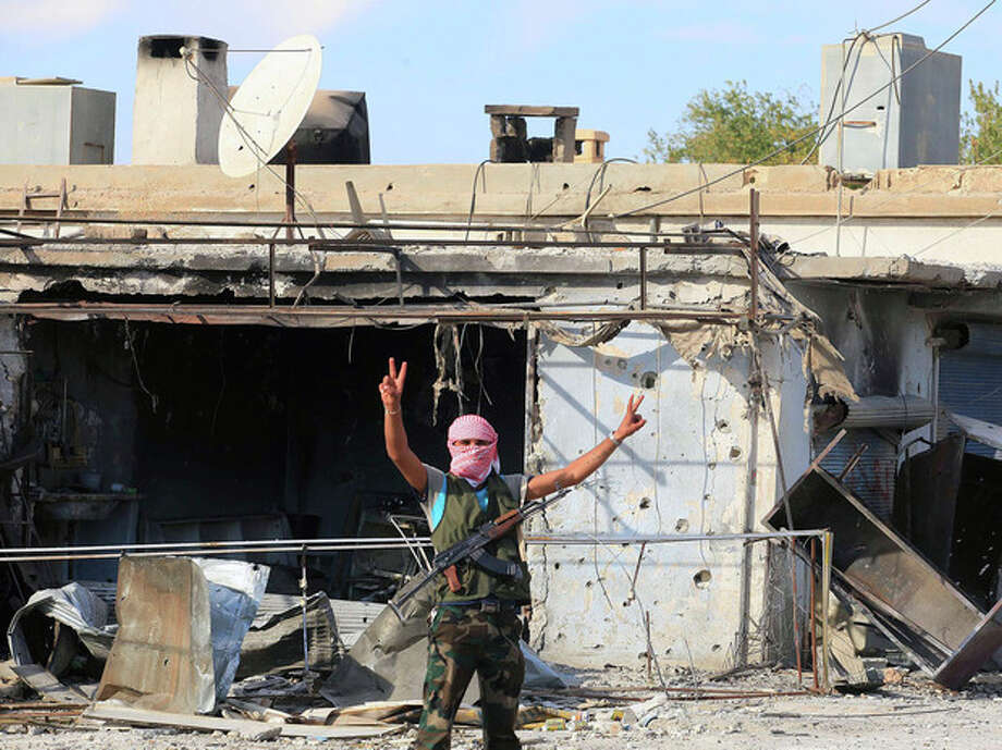 A Syrian rebel signals to the camera, in Tel Abyad, Syria, Friday, Oct. 5, 2012. On Friday, a Syrian mortar round hit inside Turkey, causing no injuries, and Turkish troops returned fire, the state-run news agency Anadolu said late Friday, and Turkey deployed more troops near to the border with Syria. (AP Photo) / AP