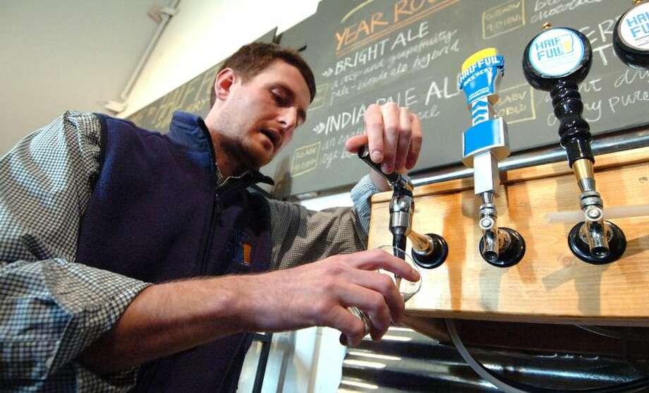 Hour Photo/ Alex von Kleydorff. Jordan Giles, Chief Beer Organizer pours a Cherry Vanilla Stout in The Tasting Room at Half Full Brewery