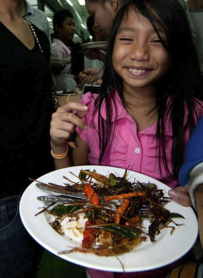 This undated photo provided by the United Nations Food and Agriculture Organization (FAO) shows a woman holding a plate with insects during an insect cuisine competition at an unknown location in Laos. The U.N. has new weapons to fight hunger, boost nutrition and reduce pollution, and they might be crawling or flying near you right now: edible insects. The Food and Agriculture Organization on Monday, May 13, 2013, hailed the likes of grasshoppers, ants and other members of the insect world as an underutilized food for people, livestock and pets. A 200-page report, released at a news conference at the U.N. agency's Rome headquarters, says 2 billion people worldwide already supplement their diets with insects, which are high in protein and minerals, and have environmental benefits. (AP Photo/Thomas Calame, FAO, ho)