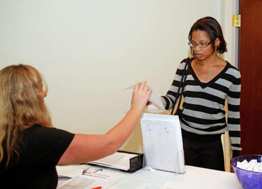 Kiara Joyner hands over her resume during a job fair held by fairfieldcountyjobs.com at 535 Connecticut Avenue Thursday evening.Hour Photo / Danielle Robinson