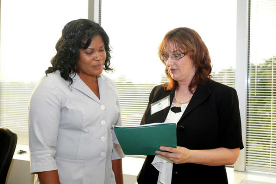 Arlene Walsh and Janice Tantimonico from Charter Oak Communities talk over a job application during a job fair held by fairfieldcountyjobs.com at 535 Connecticut Avenue Thursday evening.Hour Photo / Danielle Robinson