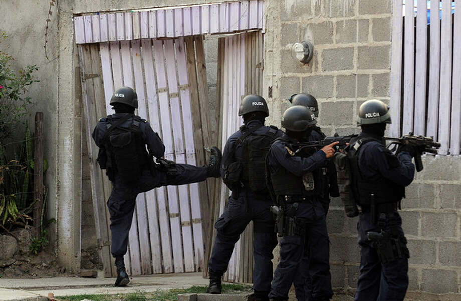 In this April 7, 2013 photo, police break into a home during a shootout that ended in two suspects killed and one officer injured as police carry out an offensive against gang members in Tegucigalpa, Honduras. The officers had surrounded a house where two gangsters had holed up after a chase with police. (AP Photo/Fernando Antonio) / AP