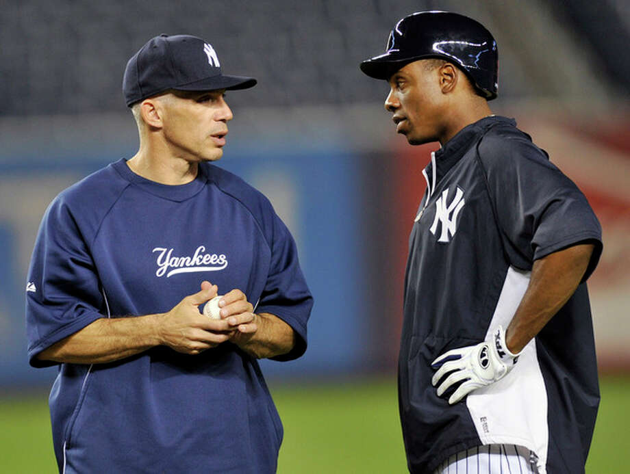 New York Yankees manager Joe Girardi, left, talks with Curtis Granderson during baseball practice Friday, Oct. 5, 2012, at Yankee Stadium in New York for an American League division series. (AP Photo/Bill Kostroun) / FR51951 AP
