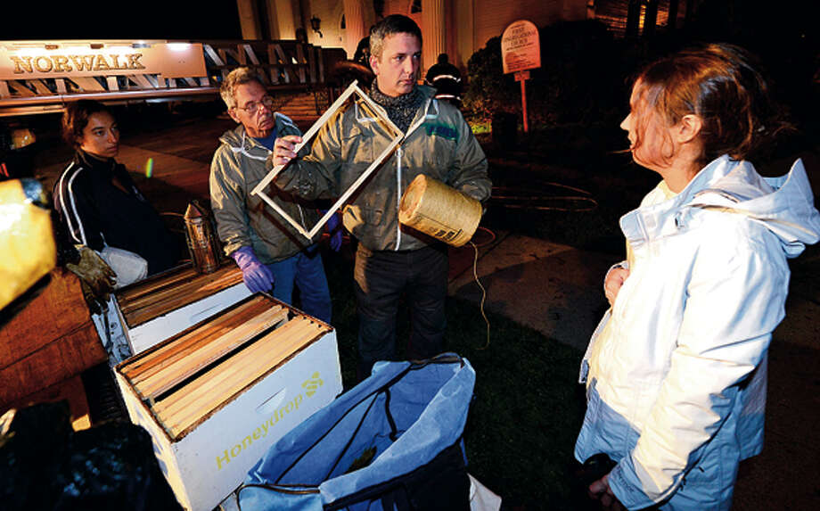 Beekeepers Andrew and Norm Cote rescue a hive of honey bees that had nested in the eaves of the steeple of the First Congregational Church on the Green in Norwalk. Hour photo / Erik Trautmann / (C)2012, The Hour Newspapers, all rights reserved