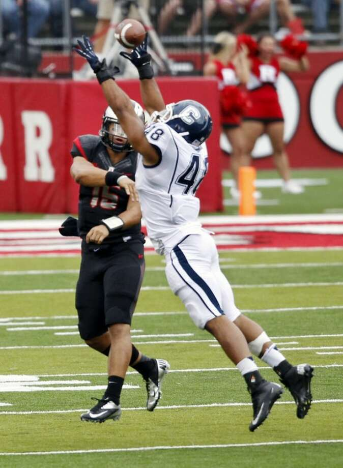 Connecticut defensive end Trevardo Williams (48) tries to block a pass by Rutgers quarterback Gary Nova during the first half of an NCAA college football game in Piscataway, N.J., Saturday, Oct. 6, 2012. (AP Photo/Mel Evans)