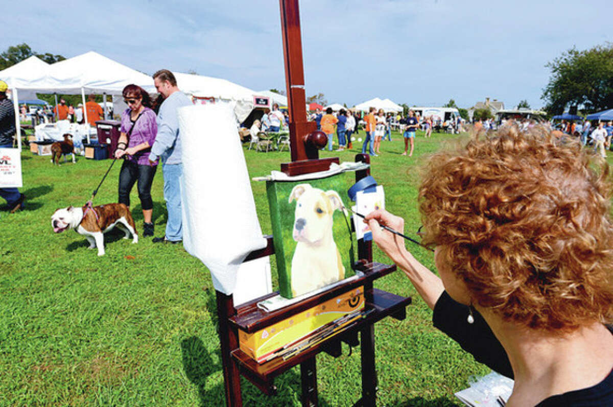 Pet Artist Shelley Lowell paints dog portraits as people and their pets enjoy the PAWS 50th Anniversary festival at Taylor Farm Park in Norwalk saturday. Hour photo / Erik Trautmann