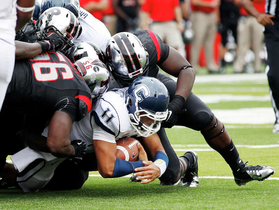 Connecticut quarterback Scott McCummings (11) holds onto the ball as he is tackled by Rutgers defenders during the first half of an NCAA college football game in Piscataway, N.J., Saturday, Oct. 6, 2012. (AP Photo/Mel Evans) / AP