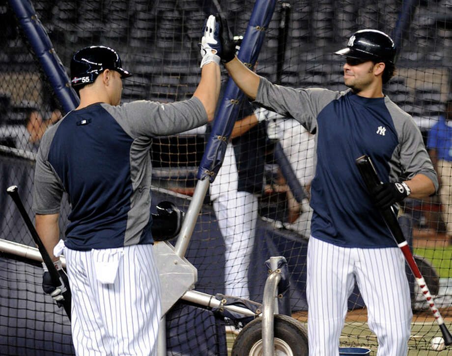 New York Yankees' Nick Swisher, right, and Russell Martin high-five during baseball practice Friday, Oct. 5, 2012, at Yankee Stadium in New York for the American League division series. (AP Photo/Bill Kostroun) / FR51951 AP